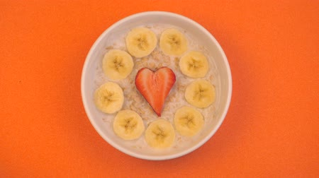 oat flakes : Womans hands putting some strawberries by ceramic bowl with oatmeal porridge with bananas and strawberry