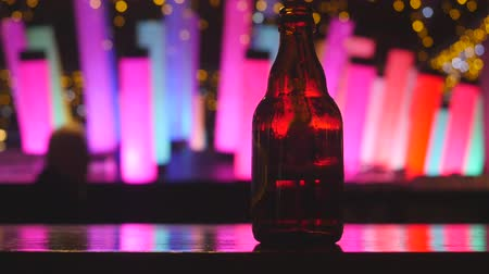 cognac : Dark glass beer bottle at the bar counter with colour changing decoration glowing flashing lamp cylinder column fluorescent neon on background Stock Footage