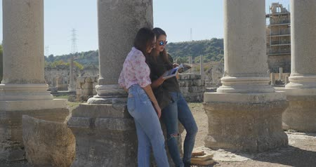 antikvitás : Young women tourist watching travel guide in Ancient city Perge with antique colonnada ruins of ancient temple roman architecture on background. This is open air antique historical museum in Turkey Stock mozgókép