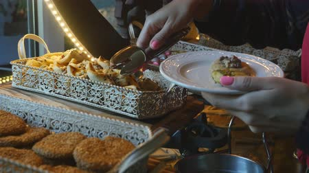assar : Food buffet in a luxury hotel. Closeup of womans hand taking some cookies in slow motion