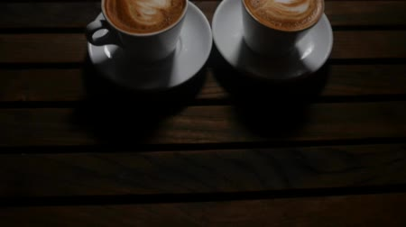 cabeçalho : Closeup view of white cup of coffee with milk heart over wooden background in dark place. Coffee time concept