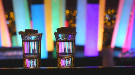 lindeboom : Two silver tequila shots with lime on bar counter with color changing  led tube lamps closeup view
