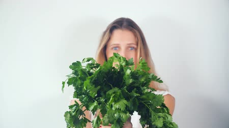 голова и плечи : Studio portrait of a beautiful happy smiling young woman with a bouquet of fresh greenery - parsley Стоковые видеозаписи