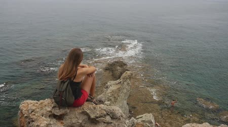 zingeving : Female tourist with backpack sitting on a rock on clear sky and calm Mediterranean sea background. She is lonely and thinking about meaning of life.