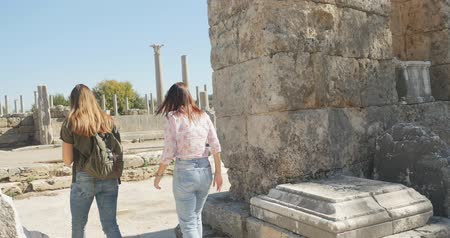antikvitás : Young women tourist walking with map in Ancient city Perge with antique colonnada ruins of ancient temple roman architecture on background. This is open air antique historical museum in Turkey Stock mozgókép