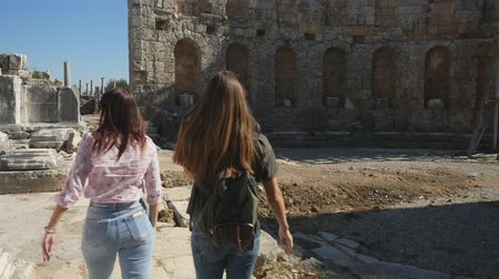 antiquities : Young women tourist walking with map in Ancient city Perge with antique colonnada ruins of ancient temple roman architecture on background. This is open air antique historical museum in Turkey Stock Footage