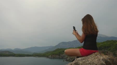 significado : Female tourist taking pictures on mobile phone sitting on a rock on clear sky and calm Mediterranean sea background. Catching good moments of life