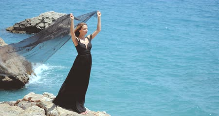 меланхолия : Beautiful woman standing on rock in elegant black dress and holding black scarf about her head