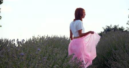 изобилие : Young woman in pink skirt walking in the lavanda field on the sunset