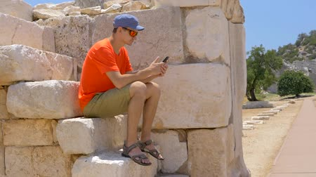 описание : Young man sitting on the stones and looking at phone in the ancient Agora in archaeological site of Patara, part of Lycian way in Turkey Стоковые видеозаписи