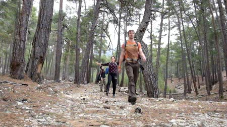 tauro : Happy hikers walking towards the Tahtali mountain peak in Turkey, Antalya province wearing hiker backpacks. Tahtali mountain is 2365m high.