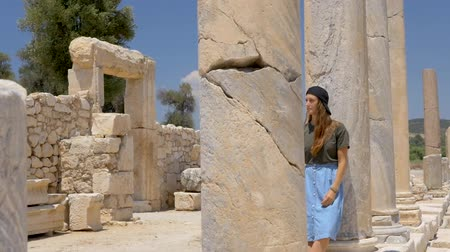 prozkoumat : Woman tourist walking in colonnaded street of ancient greek agora in Patara, Turkey
