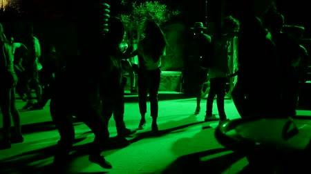 hiphop : Unrecognizable people dancing outdoors under green light