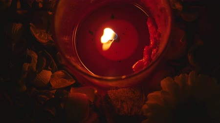 сжигание : Closeup of melted red candle lighting in the night