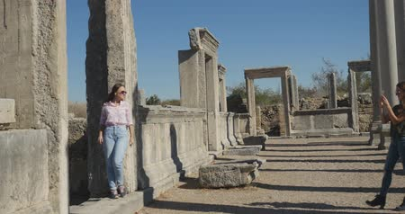 starožitnosti : Young tourist taking picture in Ancient city Perge with antique colonnada ruins of ancient temple roman architecture on background. This is open air antique historical museum in Turkey Dostupné videozáznamy