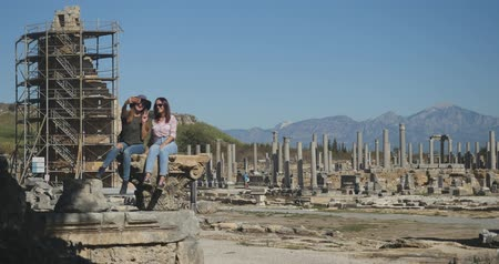 amphitheatre : Young smiling women taking selfie in Ancient city Perge with antique colonnada ruins of ancient temple roman architecture on background. This is open air antique historical museum in Turkey