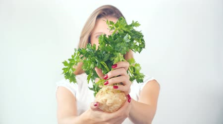 zeller : Defocused young woman holding in hands with red manicure fresh celery root Stock mozgókép