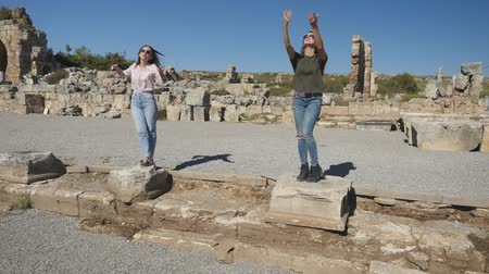 starožitnosti : Young smiling girls posing on the column ruins ancient city Perge on background. Imagine a statue. Dostupné videozáznamy