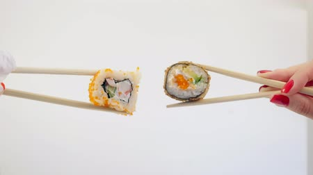 prawns : Two hands hold uramaki and baked sushi with chopsticks on white background Stock Footage