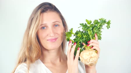 zeller : Young pretty blue-eyed woman holding in hands with red manicure fresh celery root and smiling at camera Stock mozgókép