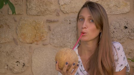 coquettish : Young smiling blue-eyed caucasian woman drinking coconut water on yellow stone wall background. Giving coconut to you Stock Footage
