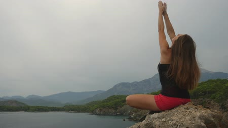 anlamı : Girl practices yoga near the ocean during sunrise time, lotus pose, focus on the sea Stok Video