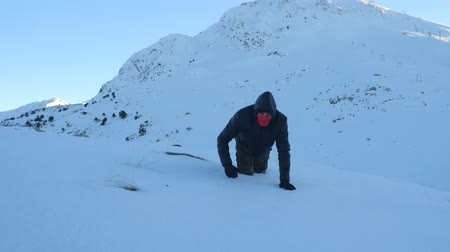 antalya : Young man in dark clothes falling down exhausted on a snowy mountain, sunset time