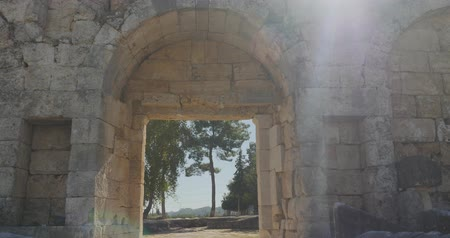 archeologie : Camera moving through ancient arch in the wallin Ancient city Perge with antique temple ruins of ancient temple roman architecture on background. This is open air antique historical museum in Turkey