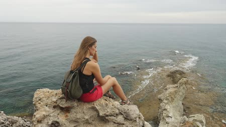 anlamı : Female tourist with backpack sitting on a rock on clear sky and calm Mediterranean sea background. She is lonely and thinking about meaning of life.