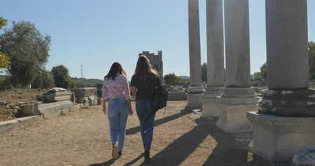 円形競​​技場 : Young women tourist walking with map in Ancient city Perge with antique colonnada ruins of ancient temple roman architecture on background. This is open air antique historical museum in Turkey 動画素材