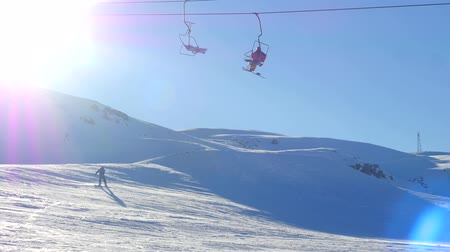 chair lift : View of moving ski lift with people and sportive people snowboarding and skiing from snowy mountain slope on background in Saklikent near Antalya, Turkey Stock Footage