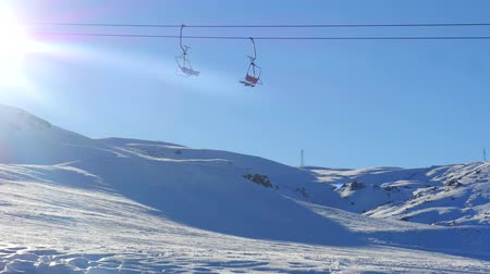 ski freestyle : View of moving ski lift and man skiing fastly from snowy mountain slope on background in Saklikent near Antalya, Turkey Vidéos Libres De Droits