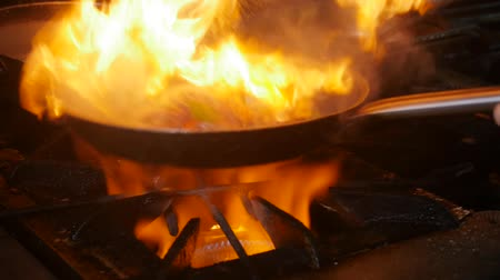 cordeiro : Chef in restaurant kitchen at stove with pan, doing flambe on food. Fire in the kitchen. Fire gas burn is cooking on iron pan,stir fire very hot Vídeos