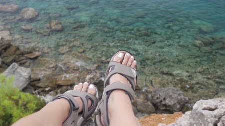 terlik : Woman with trekking sandals sitting on rock high above the sea Stok Video