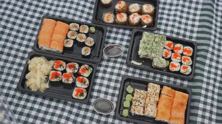 soya : Overhead View of sushi eating process by group of people on picnic cloth in fast motion. Different sushi sets with soya souse and wassibi.