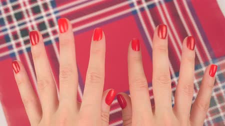bordeauxdog : Womans hands with red manicure appear on red christmas background, finger movements Stockvideo