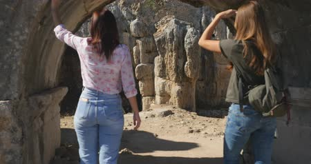 starožitnosti : Young women tourist walking in Ancient city Perge with antique colonnada ruins of ancient temple roman architecture on background. This is open air antique historical museum in Turkey