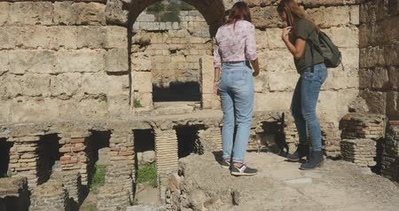 antikvitás : Young tourist taking picture in Ancient city Perge with antique colonnada ruins of ancient temple roman architecture on background. This is open air antique historical museum in Turkey Stock mozgókép