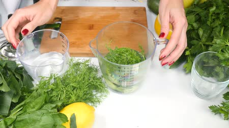 цуккини : Womans hands preparing healthy green cocktail adding water and mixing ingredients using hand blender. Healthy eating concept. Greenery on white table.