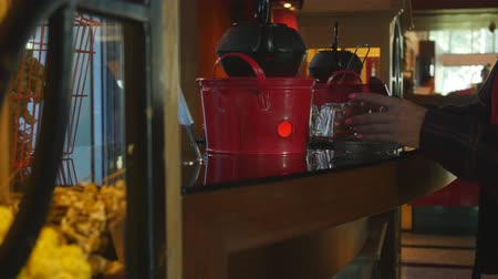 aksan : Unrecognized woman brew tea from brown teapot standing on a pink steel heater with a candles and glass  tea mug. Hotel self-service concept Stok Video