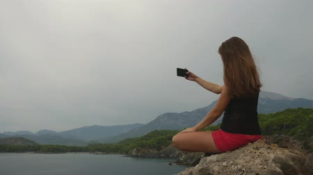 anlamı : Female tourist taking pictures on mobile phone sitting on a rock on clear sky and calm Mediterranean sea background. Catching good moments of life