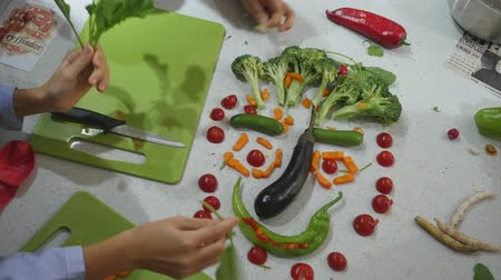 art culinaire : Closeup view of childrens hands create funny cartoon face made of vegetables