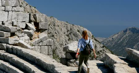 以上 : Young woman walking in amphitheater in Pisidian city Thermessos built at an altitude of more than 1000 metres near Antalya in Turkey.