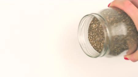 salvia : Closeup view pouring black chia seeds from glass jar