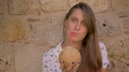 coquettish : Young smiling blue-eyed caucasian woman drinking coconut water on yellow stone wall background