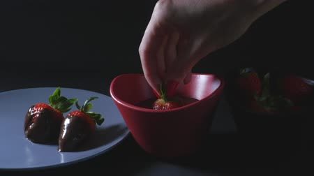 мусс : Womans hand dips strawberry into chocolate mixture and puts it on the plate Стоковые видеозаписи