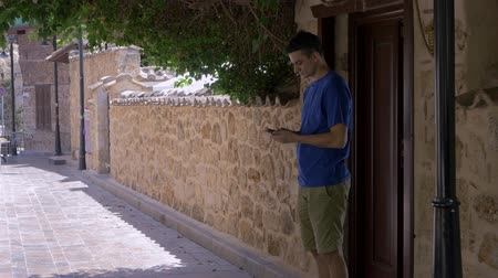 decidir : Young man comes out the wooden door and looking at smart phone deciding where to go Stock Footage