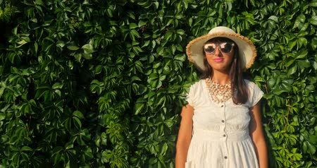 relance : Portrait of the beautiful woman in sunglasses and white dress standing against the background of a wall wild grapes. Vídeos