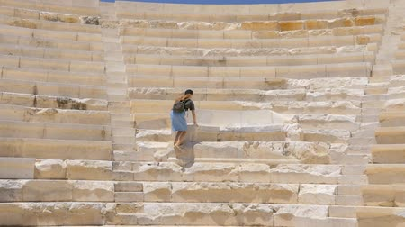 円形競​​技場 : Young pretty girl tourist sitting on the throne in an ancient greek theater