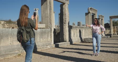 amphitheatre : Young tourist taking picture in Ancient city Perge with antique colonnada ruins of ancient temple roman architecture on background. This is open air antique historical museum in Turkey Stock Footage